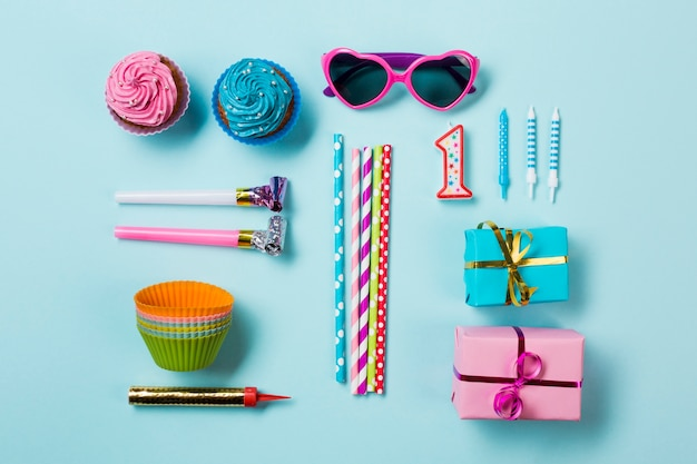 Muffins; sunglasses; party horn blowers; drinking straws; candle and gift boxes; sparkler on blue backdrop