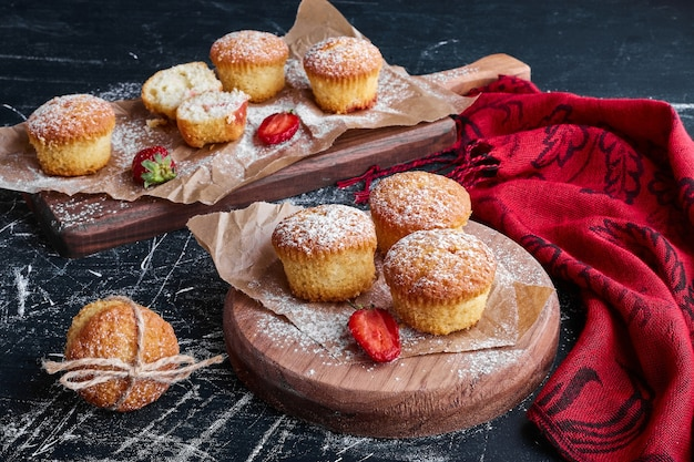Muffins with berries on wooden boards.