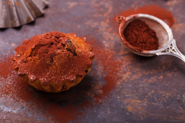 Muffins with blueberries, topped with cocoa powder, on a dark background.