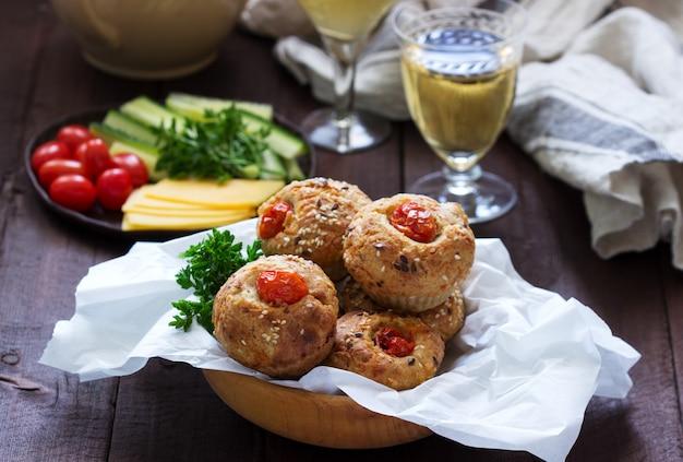 Маффины с сыром, творогом и помидорами, овощами и сыром подаются с вином.