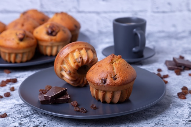 Muffins with chocolate and raisins. homemade baking.  a plate with muffins and a cup of coffee. close-up.
