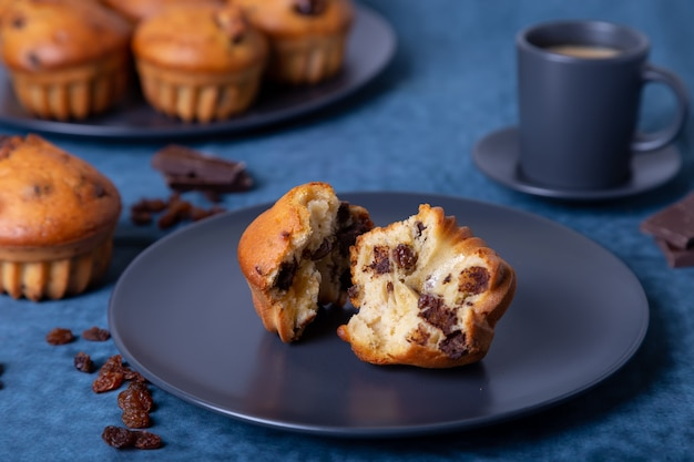 Muffins with chocolate and raisins. homemade baking.  a plate with muffins and a cup of coffee.