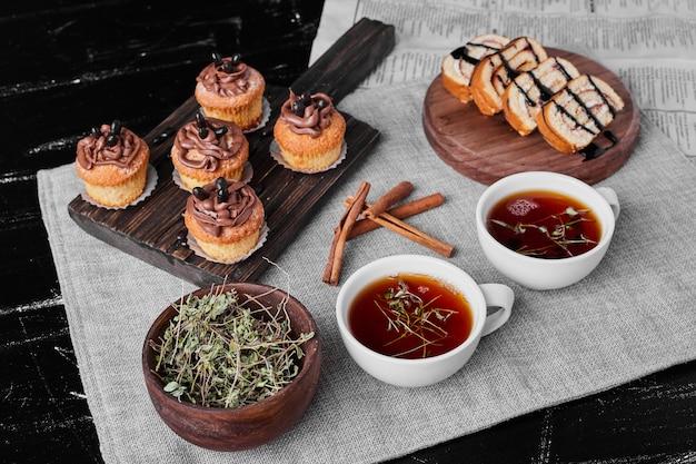 お茶とロールケーキと木の板にココアクリームとマフィン。
