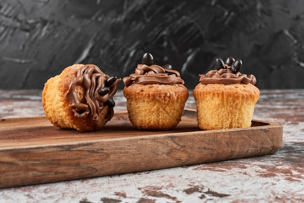 Muffins with cocoa cream on a wooden board.