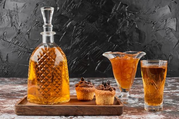 Маффины с конфитюром и напитком на деревянной доске.