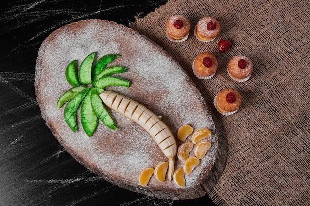 Muffin con composizione di frutta sul piatto di legno.
