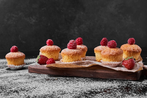 Muffins with raspberry on wooden platter.