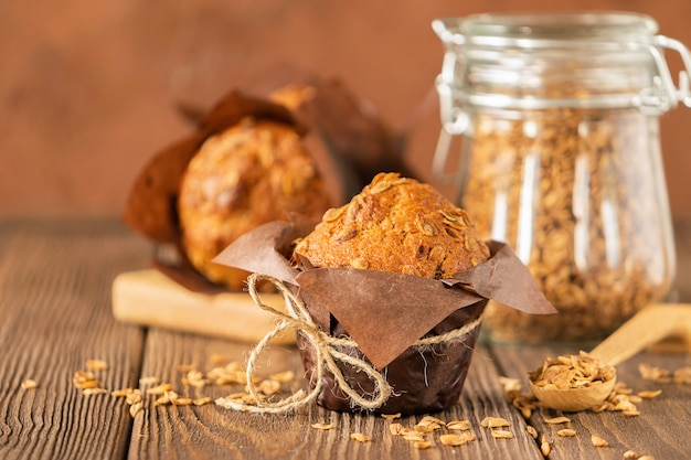Muffins with wheat flakes in brown paper packaging close-up wooden background. healthy vegan dessert.