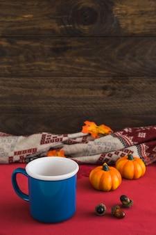 Mug and acorns near pumpkins and blanket