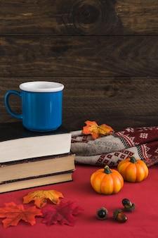 Mug and books near autumn symbols and blanket