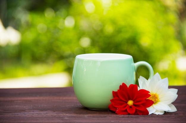 Кружка и цветы на зеленом размытом фоне