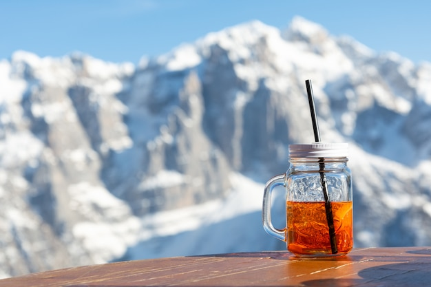 Mug aperol stands on the table of a street cafe against the backdrop of the mountains.