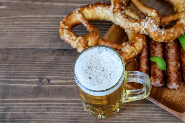 Mug of beer served with fried sausages and pretzels.
