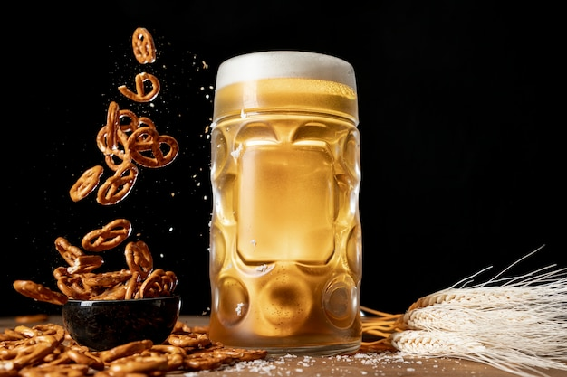 Mug of beer with falling pretzels on a table