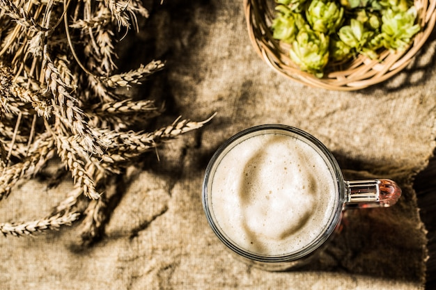 Mug beer with wheat and hops on linen cloth