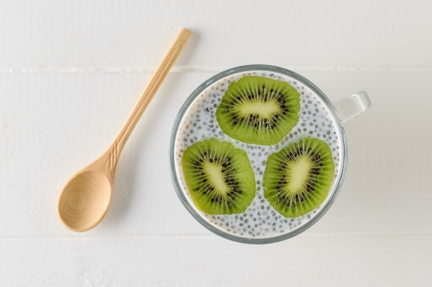 A mug of black chia seed pudding and three kiwi slices on a white wooden table. the view from the top. flat lay.