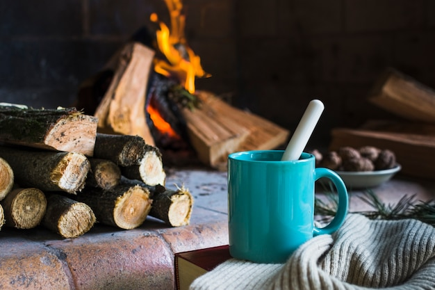 Mug and blanket near fireplace
