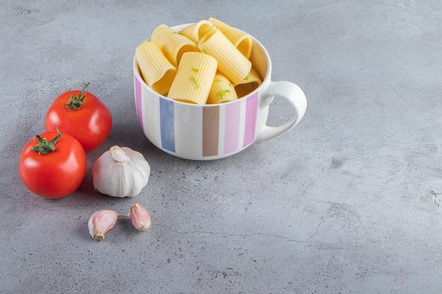 Tazza di pasta calamarata bollita con verdure su fondo di pietra.