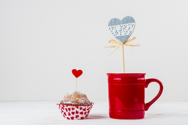 Mug and cake with ornament hearts on wands