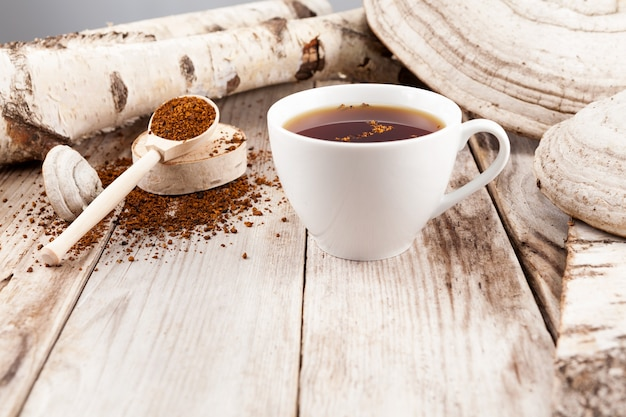 Mug of chaga tea on wooden table in a rustic style