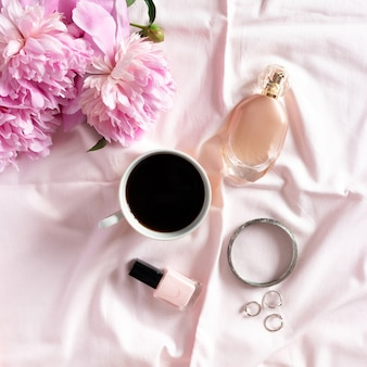 Mug of coffee, bouquet of peonies, women cosmetics and accessories on pink linen