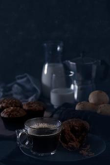 A mug of coffee, chocolate muffin, cheese bread and milk - dark food.