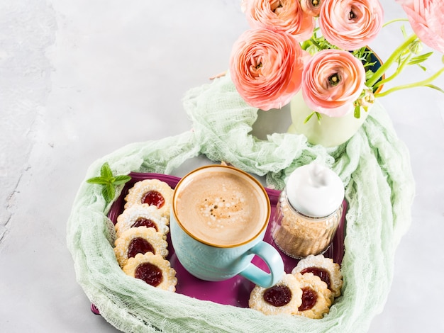 Mug of coffee cookies and pink ranunculus flowers. festive holiday breakfast. mother valentine day