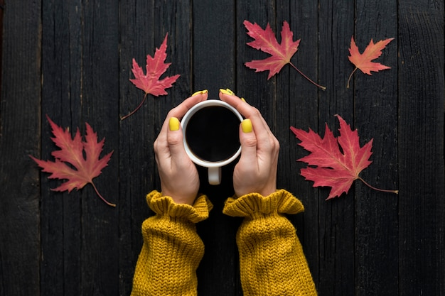 Mug of coffee in a female hand. wooden background, autumn leaves. top view