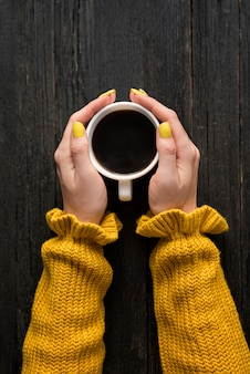 Mug of coffee in a female hands. top view
