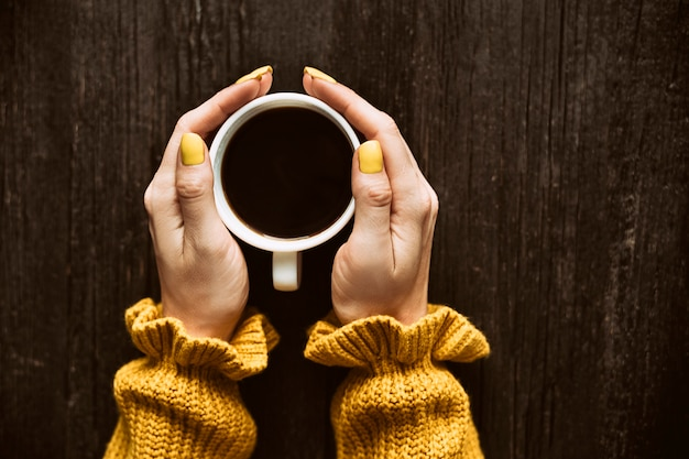 Mug of coffee in a female hands.