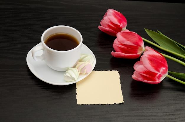 Mug of coffee and marshmallows, clean postcard, three pink tulips