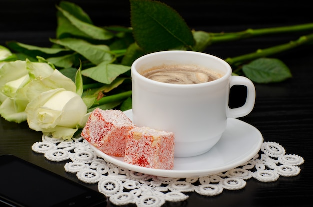 Mug of coffee with milk close-up, oriental sweets. smartphone, white roses on a black background