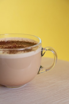 Mug of coffee with milk sprinkled with chocolate chips and foam energy and cheerfulness in morning