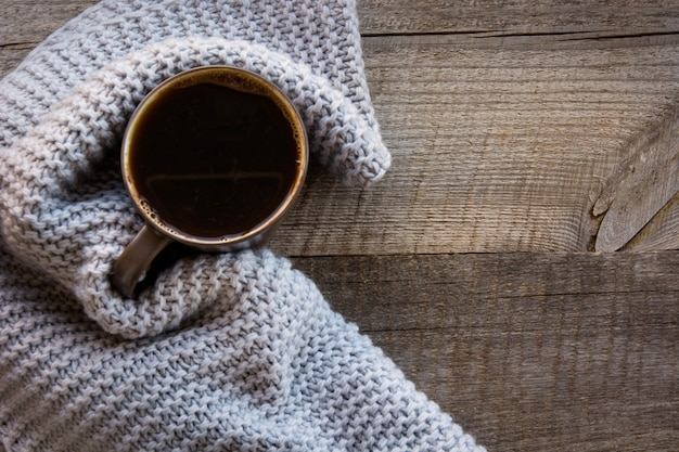Mug of coffee wrapped in warm scarf on wooden board. top view, vintage style, still life. flat lay.