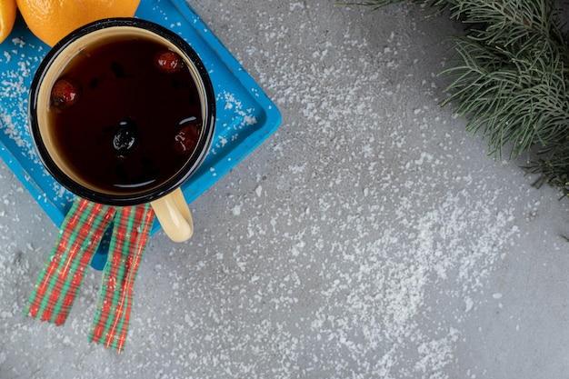Mug of dog rose tea on a platter with oranges in a festive setup on marble surface