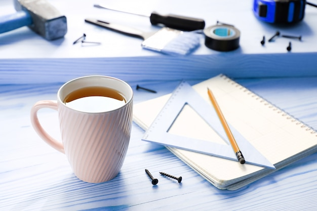 Mug, drawings and construction tools for building a house or apartment renovation.
