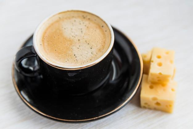 Mug of drink near cheese on table