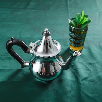 Mug of drink and silver teapot
