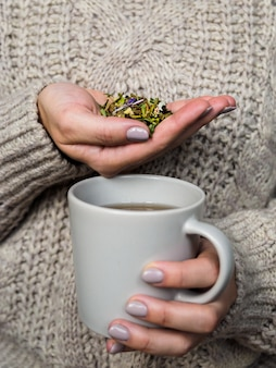 Mug and dry grass ivan-tea in the hands of the woman in sweater sipping tea with herbs. folk medicine
