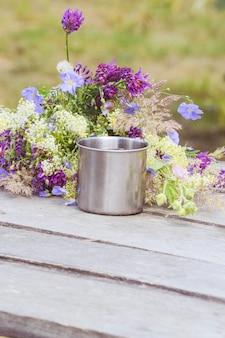 花とテーブルの上の観光客のためのマグカップ