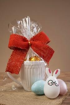 チョコレートトリュフがいっぱいで、赤い蝶ネクタイで飾られたマグカップ。