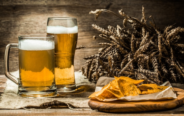 Mug, glass of beer on wooden table with wheat spikelets