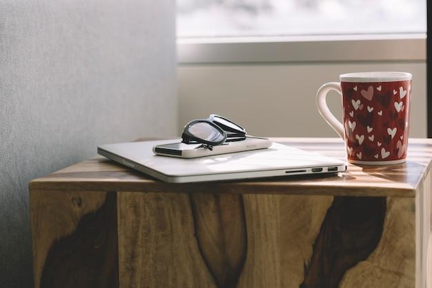 Mug and glasses near gadgets
