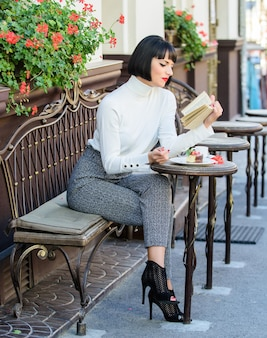 Mug of good coffee and pleasant book best combination for perfect weekend. woman have drink enjoy good book cafe terrace. self improvement concept. literature for female. girl drink coffee read book.