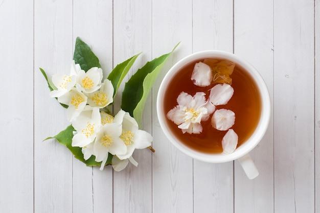 Mug of herbal tea with petals of jasmine flowers