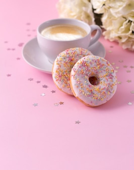 Mug of hot cappuccino and two donuts with flowers on pink