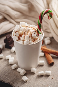 Mug of hot chocolate with marshmallow and a lollipop stick.