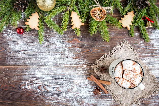 Mug of hot chocolate with marshmallow, spices, christmas ginger cookies, fir branches and cones on dark wooden background. copy space for text. christmas wallpaper, card.