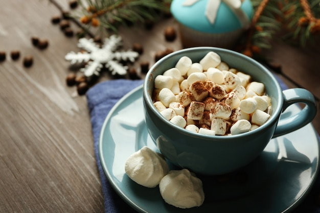 Mug of hot chocolate with marshmallows, fir tree branch on wooden surface