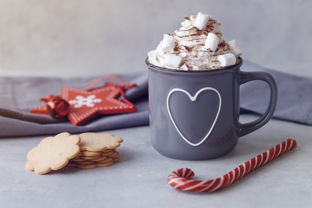 Mug of hot chocolate with whipped cream, marshmallows and red lollipop, red star, cookies on a grey background. hot winter drink